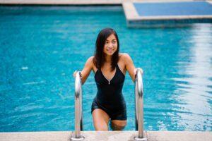 Frau benutzt Poolleiter, um aus dem Wasser zu steigen.