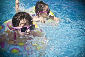 Kinder schwimmen mit Schwimmreifen in Pool mit Gegenstromanlage