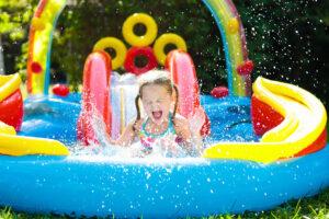 kleines Mädchen auf Wasserrutsche mit Kinderpool